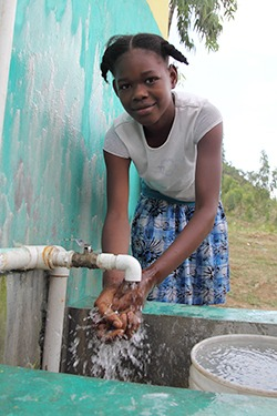 Young girl at water faucet.