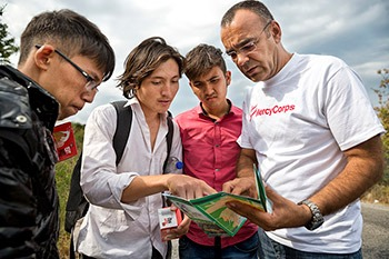 A Mercy Corps team member on the island of Lesvos, Greece shows a map to a group of refugees to help them navigate their location.