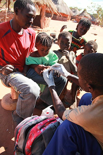 A community health worker tests a young girl for malaria using a rapid diagnostic test in Southern Province, Zambia