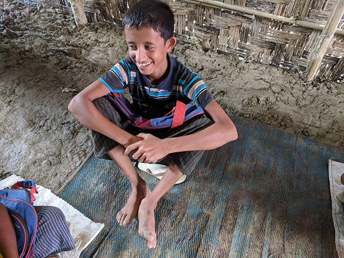 Boy sitting on mat in hut