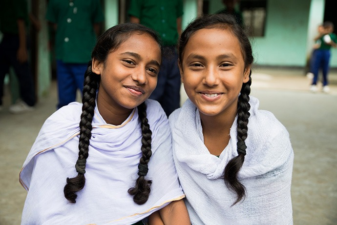 Two girls pose for a photo outside their school in Dhaka, Bangladesh