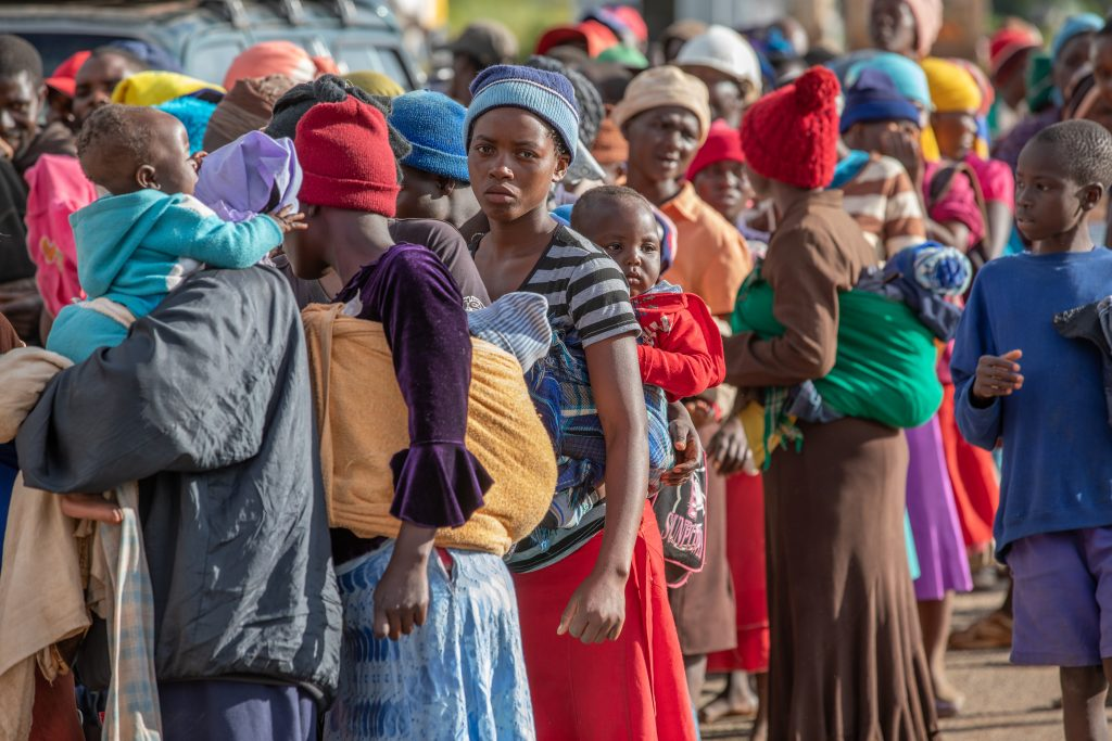 March 2019, Chimanimani, Zimbabwe. Women wait in line for food at a distribution point called Skyline, on a ridge surrounded by mudslides. (Photo credit Ezra Millstein/Mercy Corps).