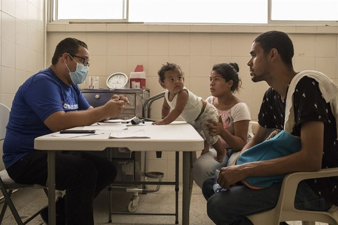 A Venezuelan couple speaks with a physician