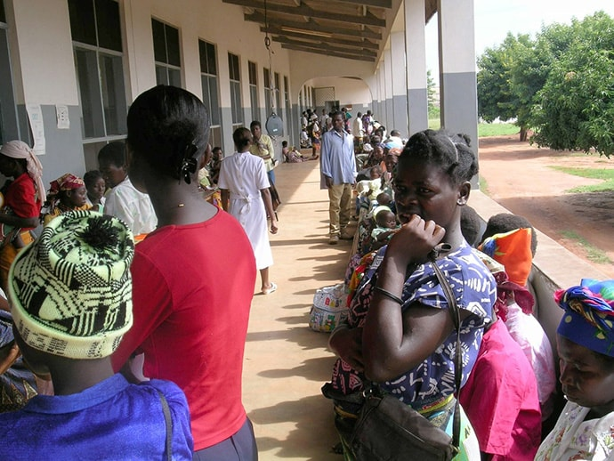 Women in Uganda wait for their turn to see a provider at a health facility