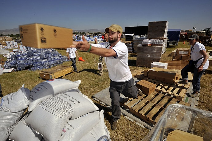 Americares relief workers unload a planeload of medicine and relief supplies