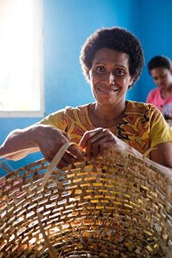 Fijian woman weaving a basket