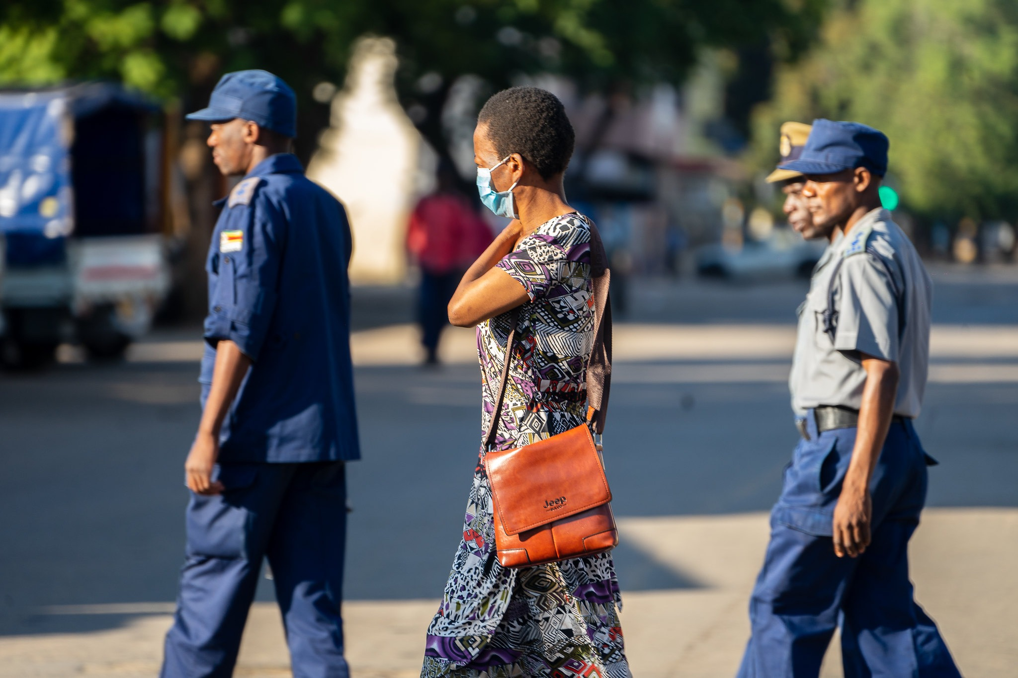 Harare, Zimbabwe. A woman wearing a COVID-19 protective mask walks past a group of police officers on patrol in Bulawayo CBD, 1 April 2020. Photo credit: KB Mpofu / ILO (CC BY-NC-ND 2.0)