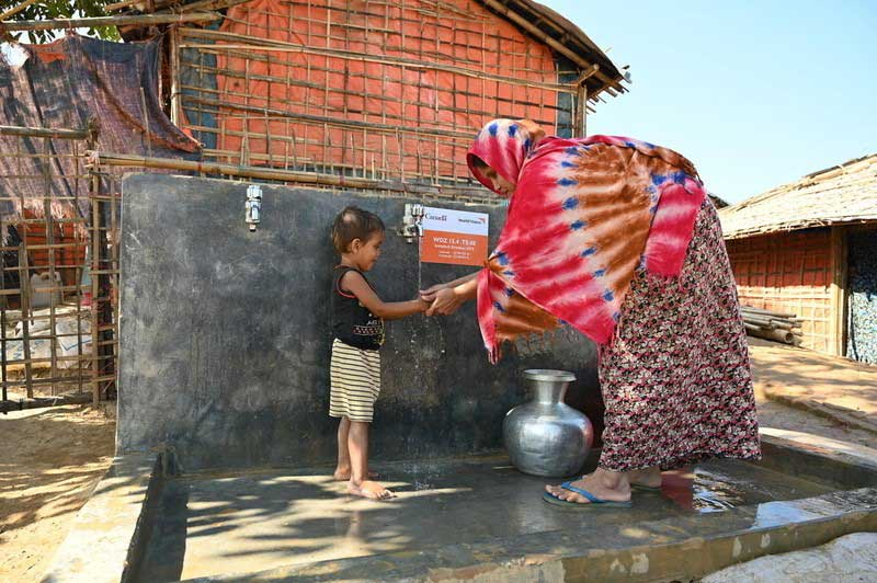 Shahanara, a mother of three, collects potable water and washes her children's hands at a water point installed by World Vision inside a refugee camp in Rohingya.