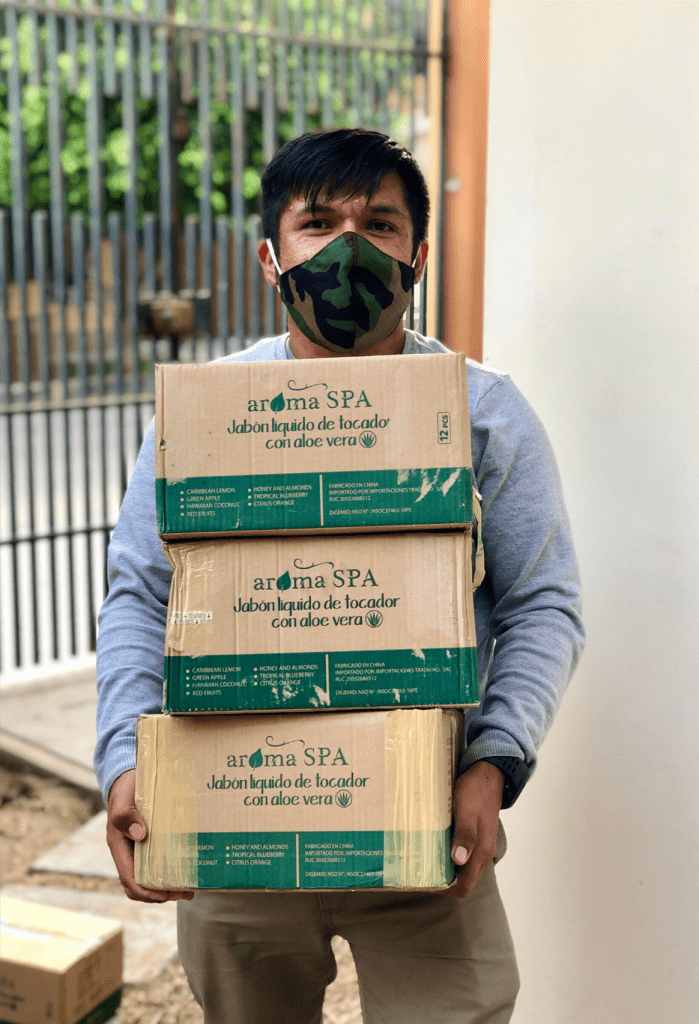 Pedro, a fisherman and youth leader in La Islila, Peru, carries boxes of donated soap to support the health of his fellow fishermen. Photo credit: Future of Fish.
