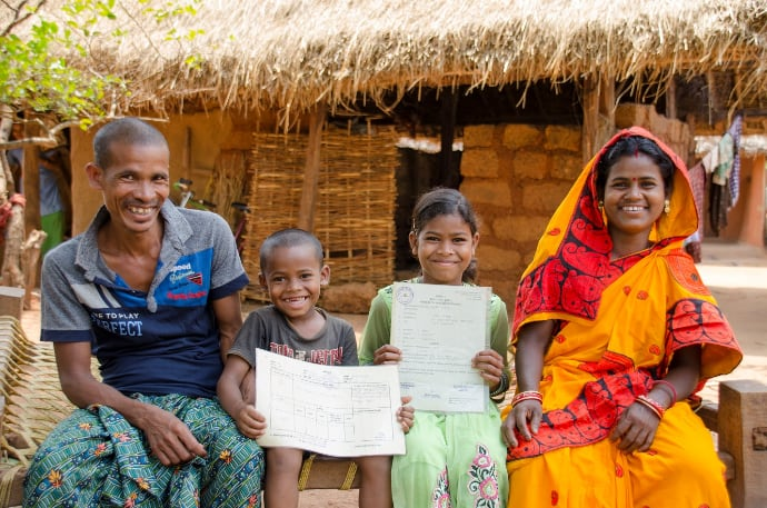 Indira and her family pose with their land title