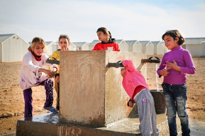 Syrian refugee children drink from water taps