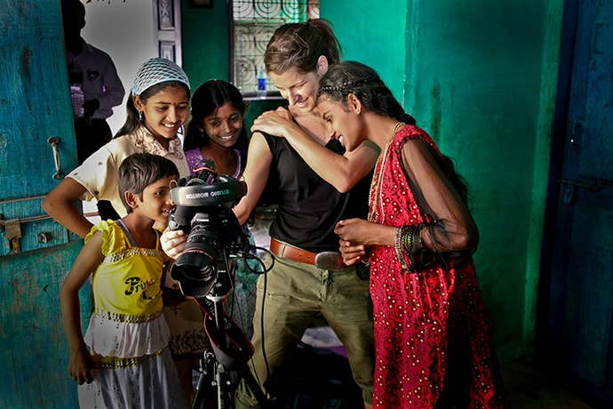 Young people inspecting camera