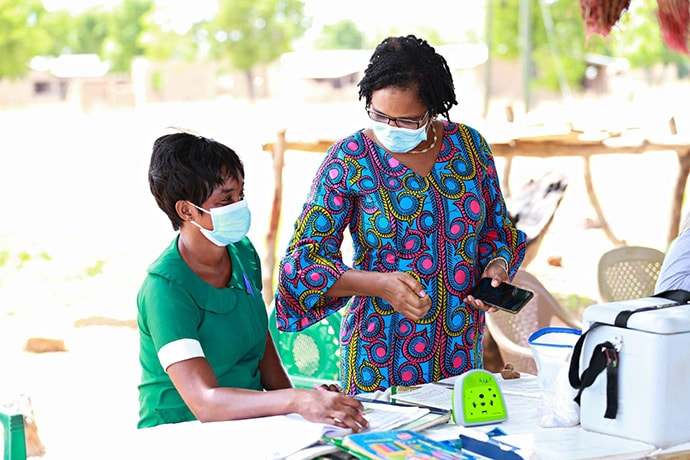 Georgina Amidu, Communication for Development Officer, UNICEF consults with a nurse