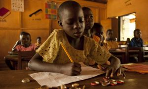 A girl uses bottle tops to count in a math lesson in Ghana. See Guardian article below