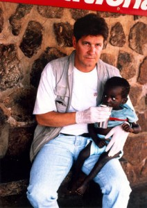 Dan in Rwanda (1994), after the mass killing crisis, helping to feed a child at the Kigali hospital