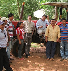 Mark Coffey (center) meets with a group of 75 Paraguayan farmers. These farmers have formed an association that sells to BioExport. They have also banded together to purchase the tractor pictured. They are hoping that their livelihoods will improve, and that they can one day become a cooperative. Photo © Global Partnerships.