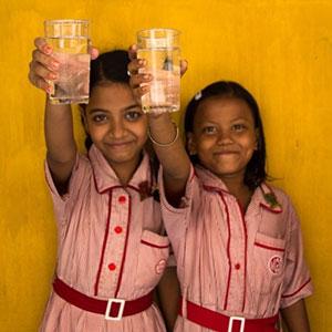 Girls holding water glasses at Splash, Murlidhar Girls School in Kolkata, India.