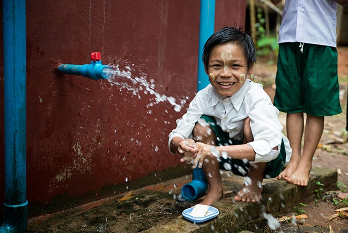 Child at water faucet.