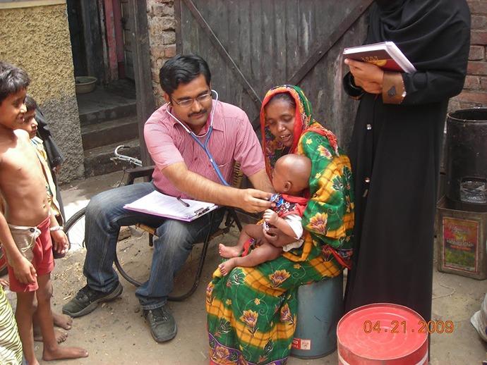 Bandyopadhyay examining an infant in Moradabad, Uttar Pradesh, India.