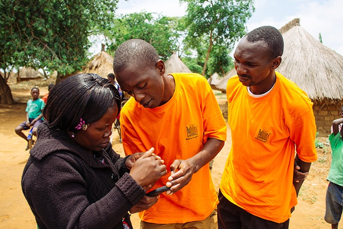 A data collector, community health worker and district malaria focal person look at a mobile phone with the village of Harmony in the background.