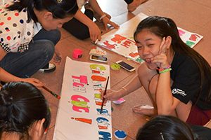 In Vietnam, a group of peer educators create signs with messages about sexual and reproductive health for a large educational event.