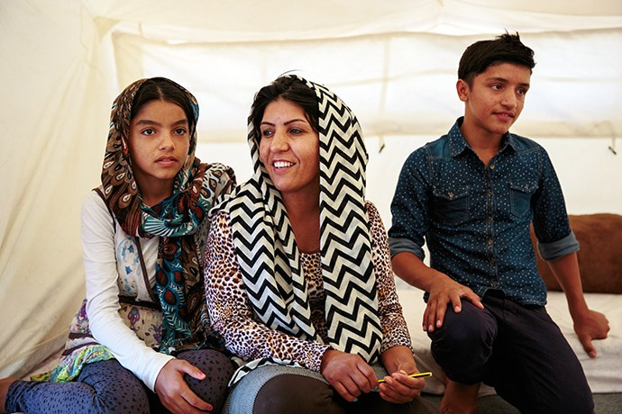 Shakila, center, fled Afghanistan with her kids, Sonia and Arash. Cash from Mercy Corps is helping them meet their urgent needs while living in Greece. (Photo: Sara Hylton for Mercy Corps).